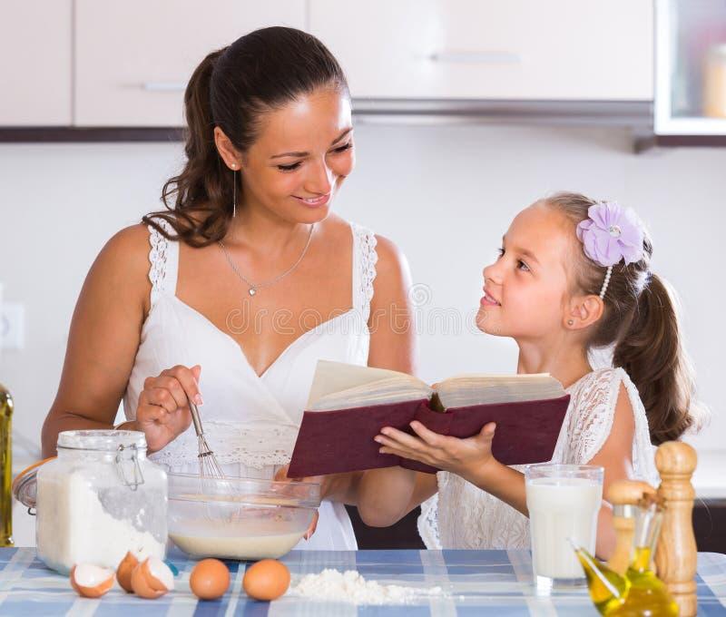 Madre de ayuda de la muchacha feliz en la cocina fotografía de archivo libre de regalías