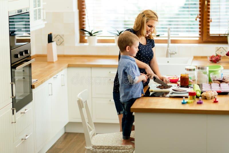 Madre de ayuda del niño lindo elegante en cocina foto de archivo libre de regalías
