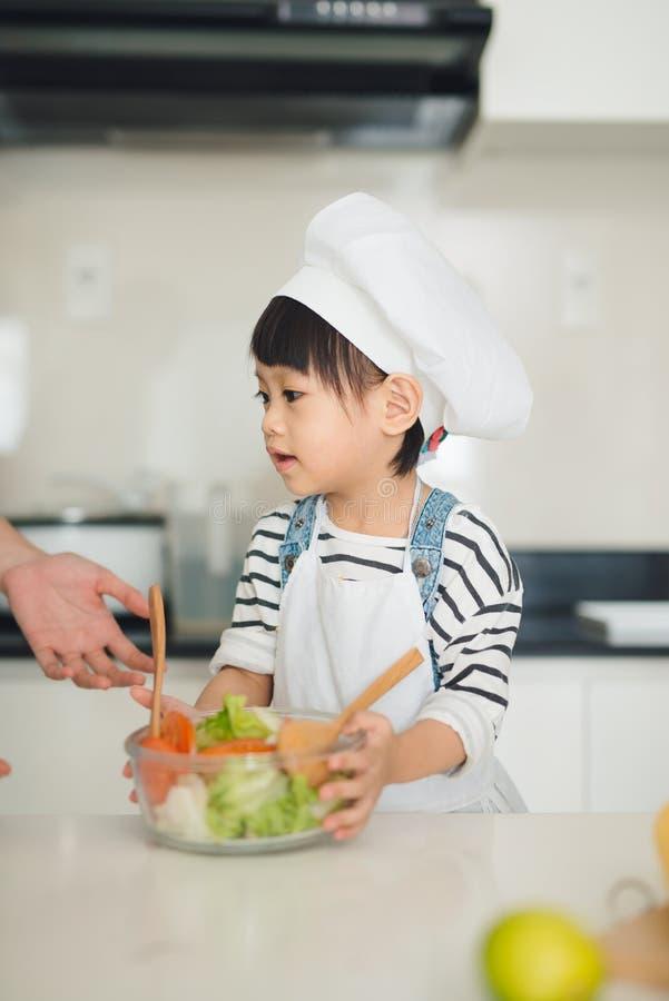 Madre de ayuda del niño que cocina en cocina moderna foto de archivo libre de regalías
