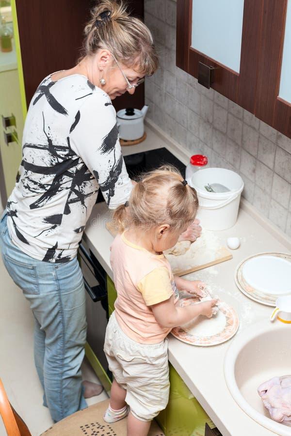 Madre de ayuda del pequeño niño a cocinar en cocina nacional foto de archivo libre de regalías