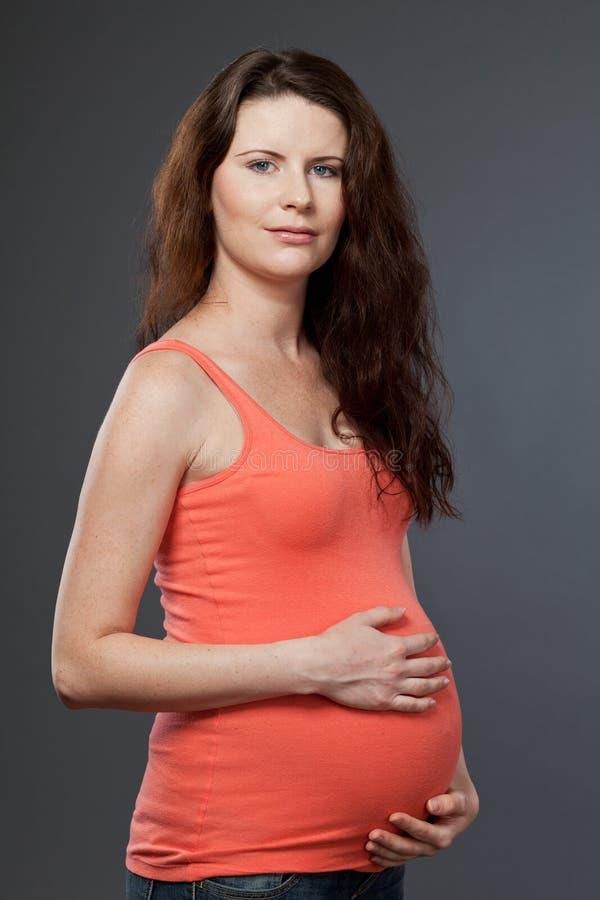 Madre de espera joven con el pelo oscuro largo. imagen de archivo
