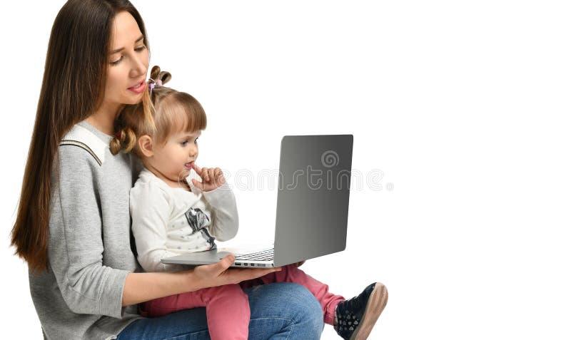 Madre de la familia e hija del niño en casa con un ordenador portátil foto de archivo libre de regalías