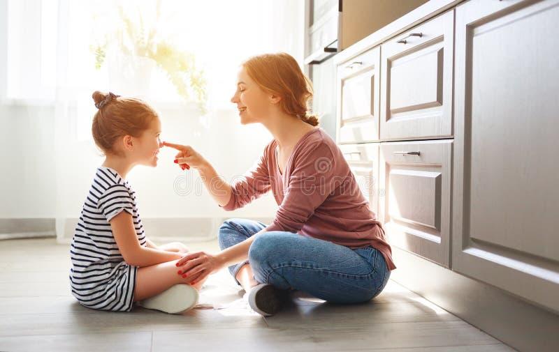 Madre de la familia e hija del ni?o que abraza en cocina en piso foto de archivo libre de regalías