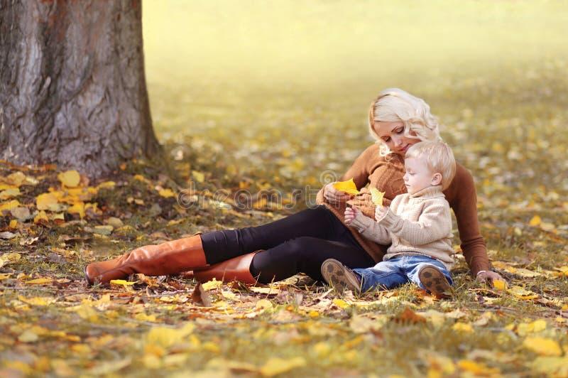 Madre de la familia que juega con el niño en parque del otoño cerca del árbol que miente en las hojas amarillas fotografía de archivo