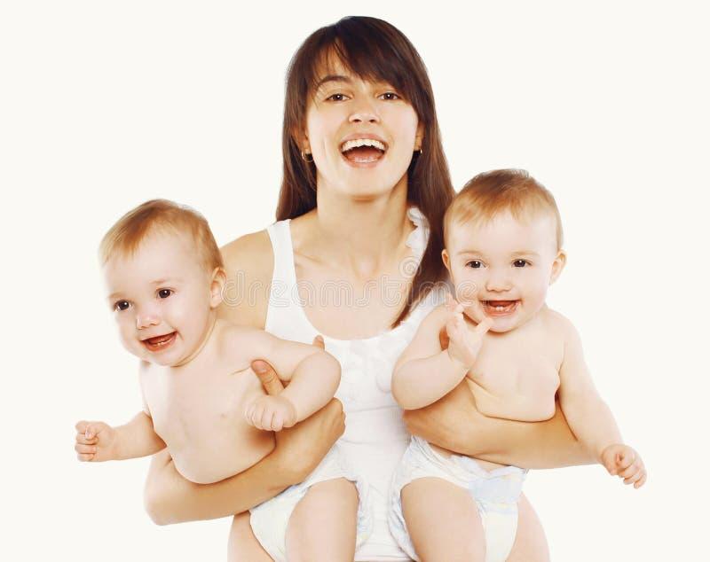 ¡Madre de la felicidad! Madre joven y dos bebés de los gemelos imagenes de archivo