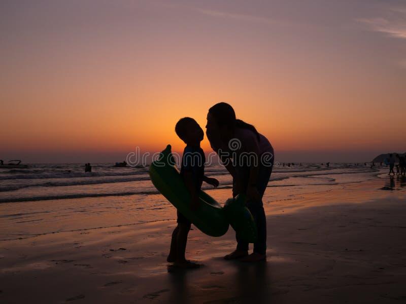 Madre de la silueta que besa al hijo en la playa con el fondo de igualación anaranjado del cielo, forma de vida de la familia imágenes de archivo libres de regalías