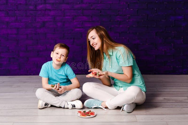 Madre de pelo largo joven e hijo de siete años en las camisas y las zapatillas de deporte que se sientan en el piso y que se divi foto de archivo