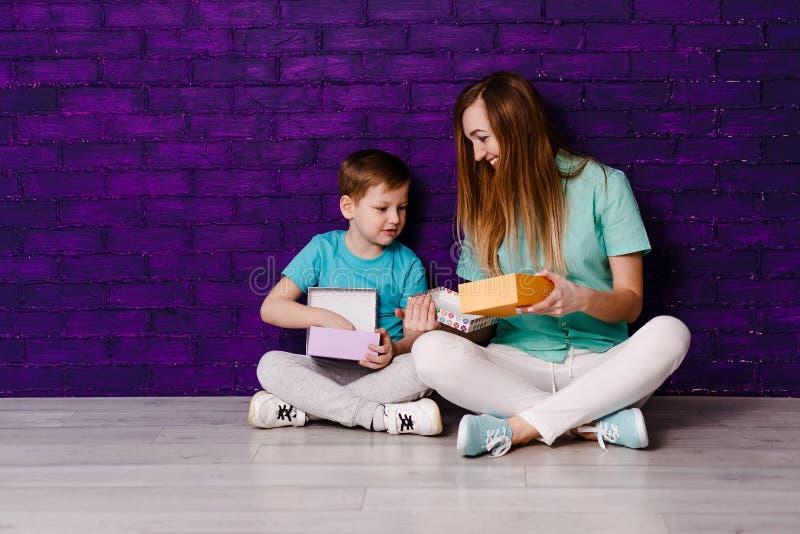 Madre de pelo largo joven e hijo de siete años en las camisas y las zapatillas de deporte que se sientan en el piso y que sostien fotos de archivo