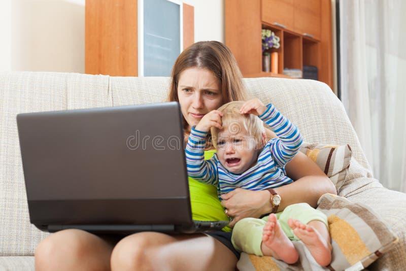 Madre de Sorehead con el bebé gritador que trabaja en línea foto de archivo libre de regalías