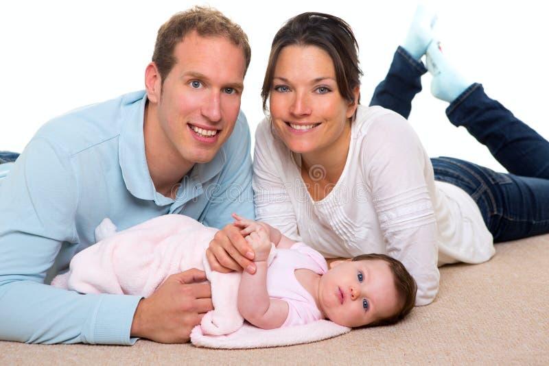 Madre del bebé y familia feliz del padre que miente en la alfombra fotografía de archivo