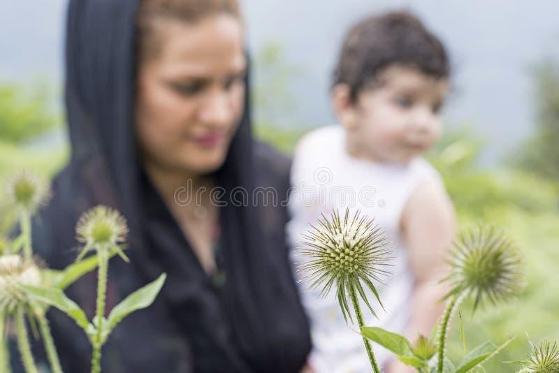 Madre del concepto de la exploración de la naturaleza y niño joven en foco al aire libre del ambiente en las plantas del primero  foto de archivo libre de regalías