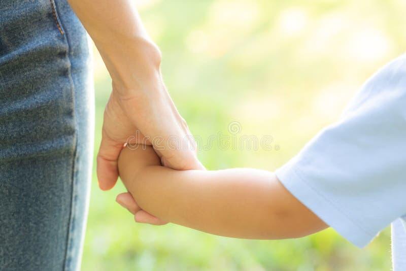 Madre del primo piano o mano della tenuta del figlio e del genitore con amore insieme nell'esterno di estate nel parco fotografia stock libera da diritti
