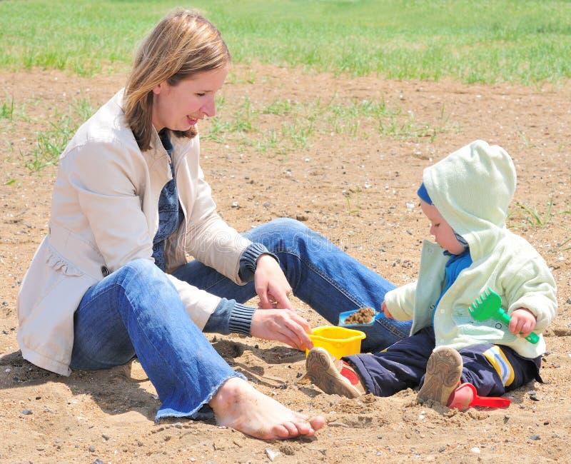 madre della famiglia del bambino che gioca sabbia immagini stock