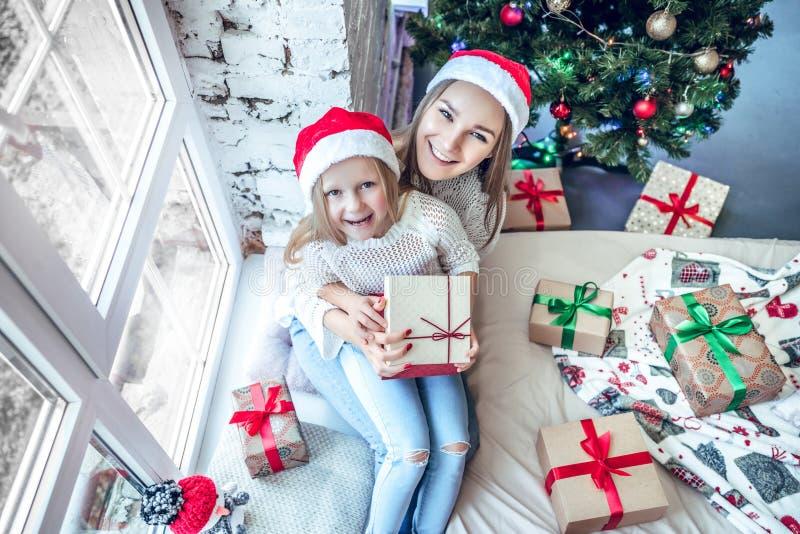 Madre della famiglia e ragazza felici del bambino vicino ad un albero di Natale con regalo di Natale immagini stock
