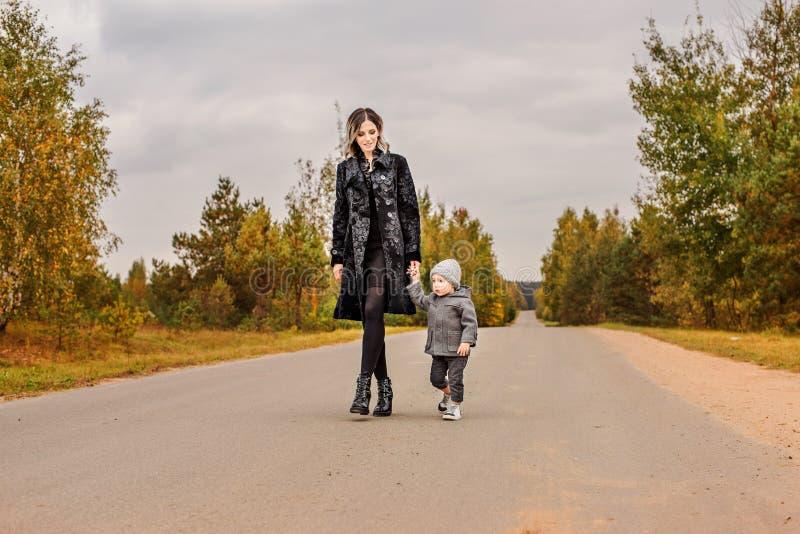 Madre della famiglia ed il suo piccolo figlio che camminano sul sentiero forestale che fa auto-stop sotto il cielo tempestoso immagini stock