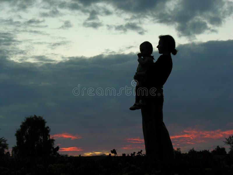 Madre della siluetta con il bambino fotografia stock
