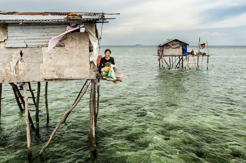 Madre della tribù di Bajau che si siede la sua casa di legno in Sabah Semporna, Malesia immagini stock libere da diritti