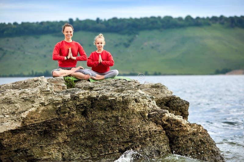 Madre deportiva e hija que hacen yoga en la roca cerca del río hermoso imagen de archivo