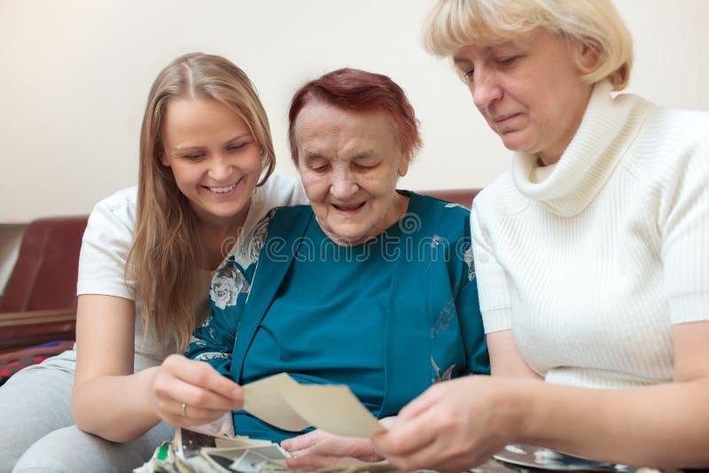 Madre, derivato e nonna esaminanti le foto fotografia stock