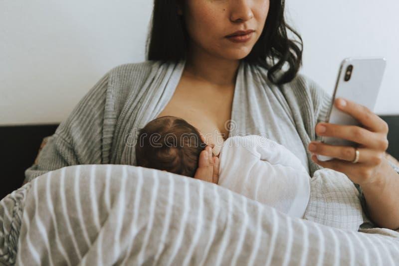 Madre di allattamento al seno che per mezzo di uno smartphone fotografie stock
