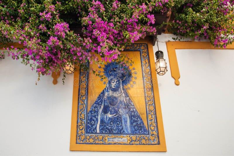 Madre di Dio sulle mattonelle variopinte all'entrata della chiesa andalusa con i fiori intorno fotografia stock libera da diritti