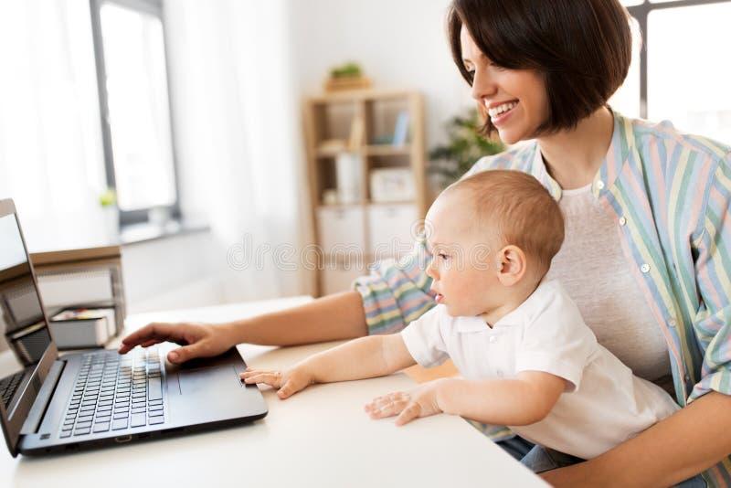 Madre di funzionamento con il neonato ed il computer portatile a casa fotografie stock