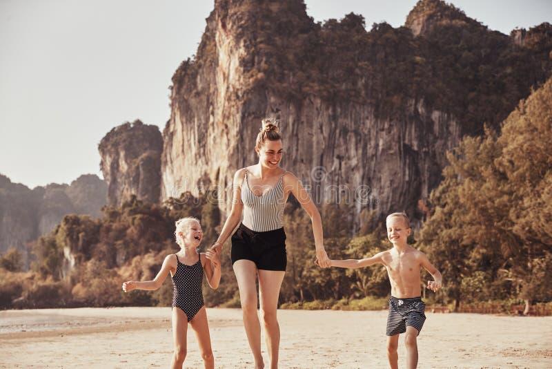 Madre di risata che si tiene per mano con i suoi bambini su una spiaggia fotografia stock
