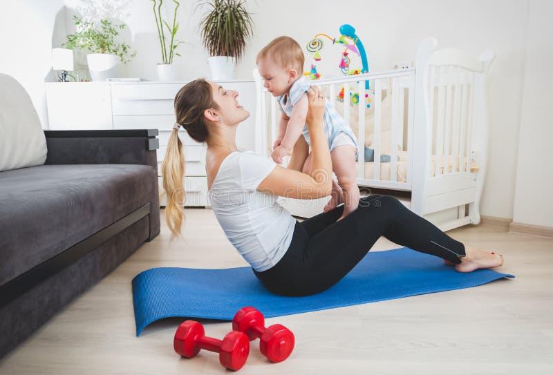Madre di SSim che gioca con il suo bambino sulla stuoia di forma fisica a casa fotografie stock libere da diritti