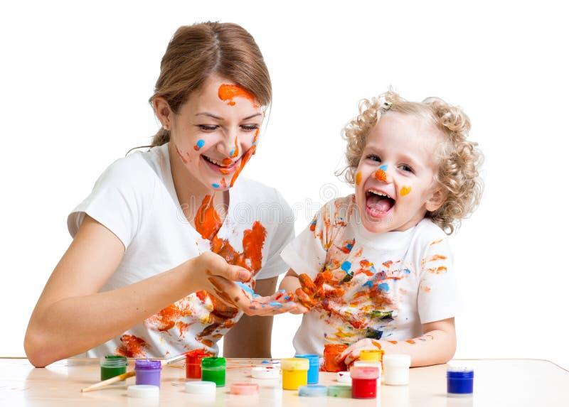 Madre divertida y niño que pintan junto imagenes de archivo