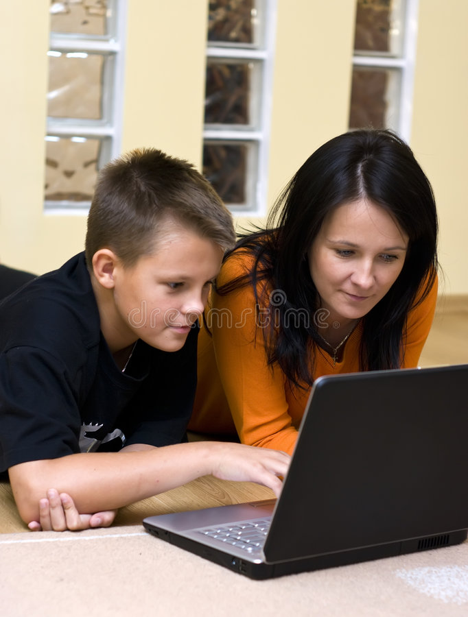 Madre e adolescente con il computer portatile fotografia stock libera da diritti