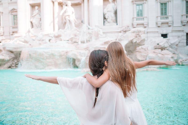Madre e bambina alla fontana di Trevi, Roma Bambina che fa un desiderio per ritornare fotografia stock