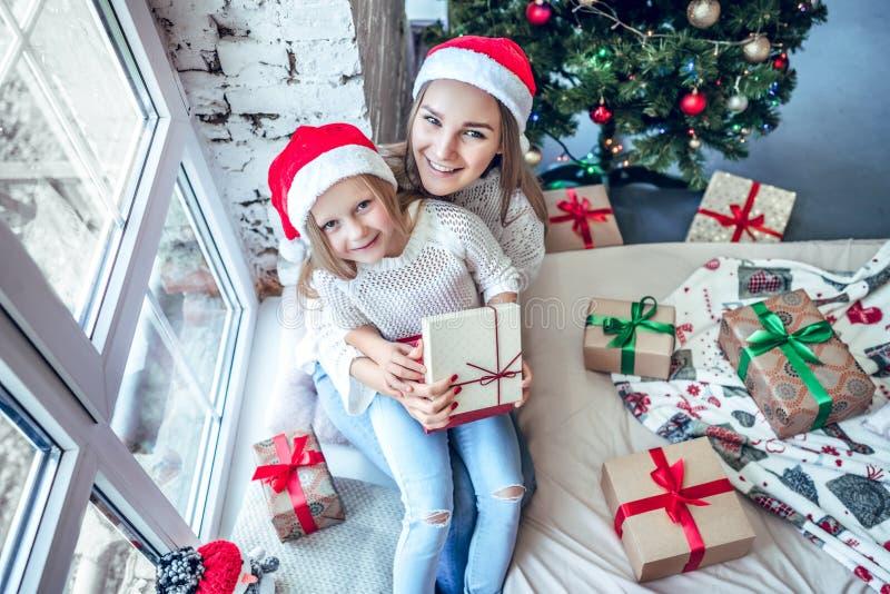 Madre e bambina felici in cappelli dell'assistente di Santa con il contenitore di regalo sopra il salone ed il fondo dell'albero  immagine stock libera da diritti