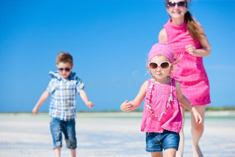 Madre e bambini che funzionano alla spiaggia fotografia stock libera da diritti