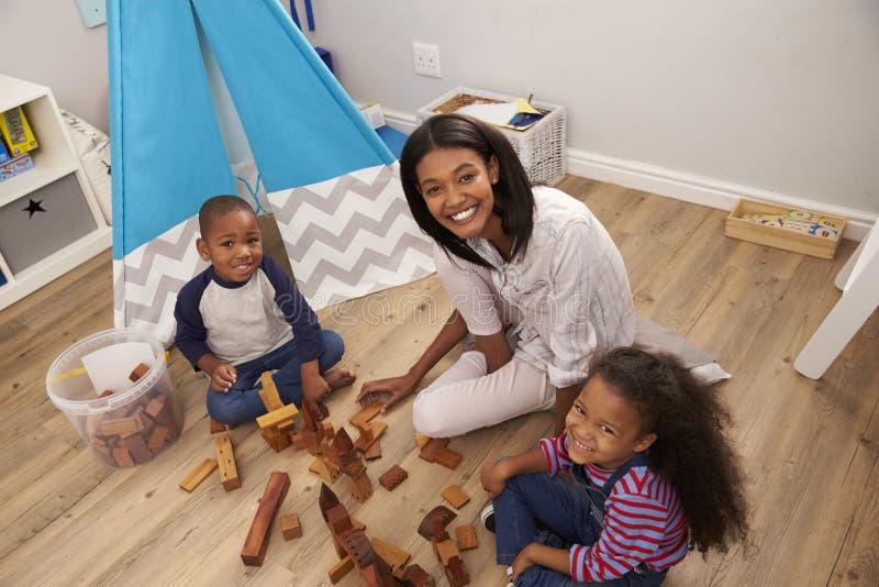 Madre e bambini che giocano con le particelle elementari in camera da letto fotografia stock