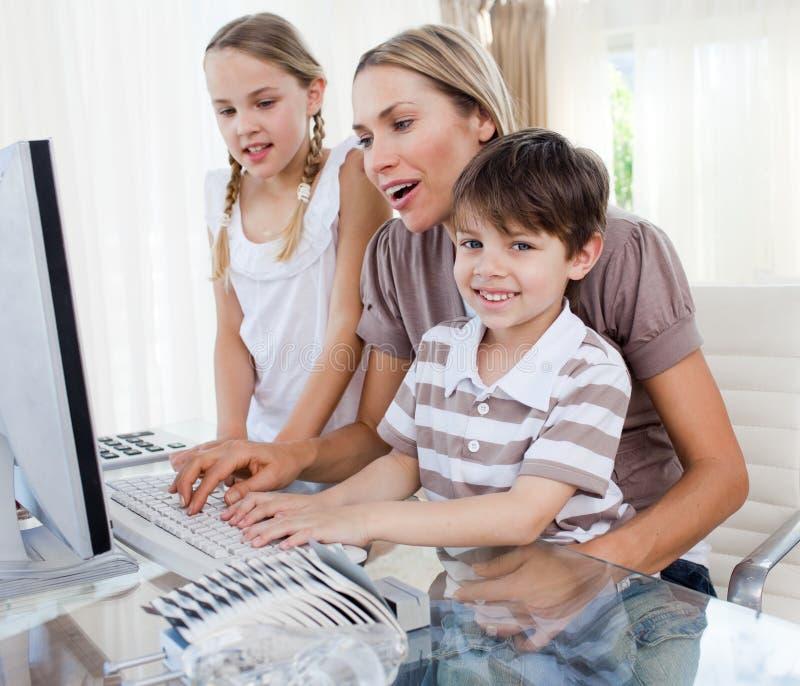 Madre e bambini che lavorano ad un calcolatore fotografia stock