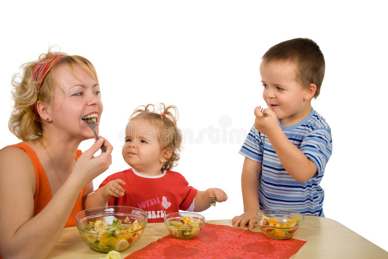 Madre e bambini che mangiano l'insalata di frutta fotografie stock libere da diritti