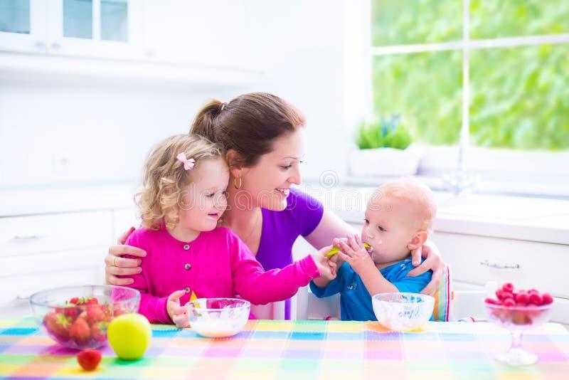 Madre e bambini che mangiano prima colazione fotografia stock libera da diritti