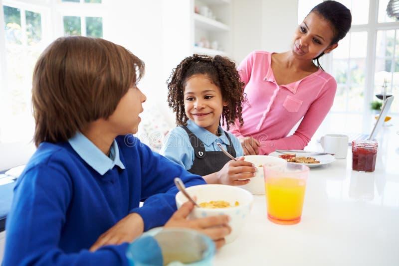 Madre e bambini che mangiano prima colazione prima della scuola immagini stock