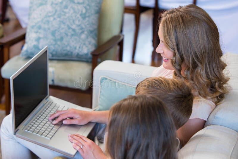 Madre e bambini che per mezzo del computer portatile sullo strato fotografia stock
