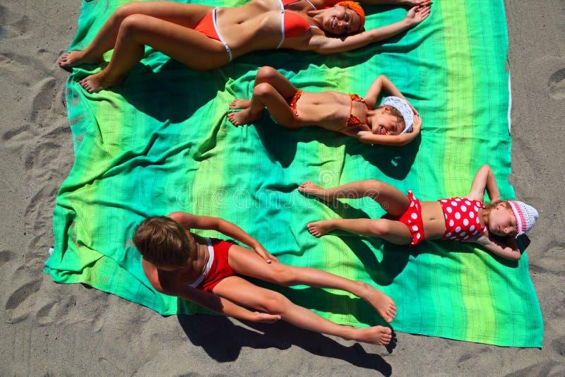Madre e bambini che si trovano sul coverlet sulla spiaggia fotografia stock libera da diritti