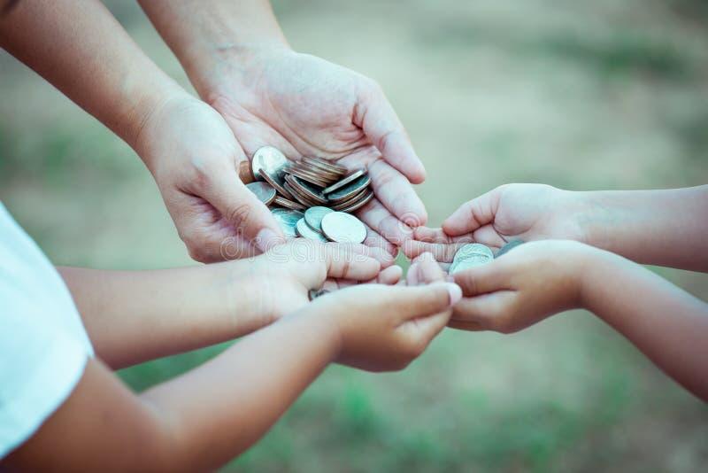 Madre e bambini che tengono moneta in mani immagini stock libere da diritti