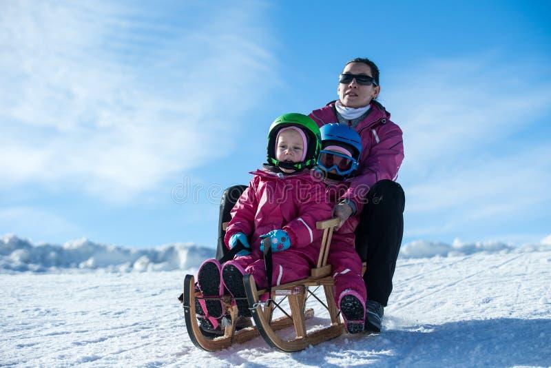 Madre e bambini divertendosi sulla slitta con la vista panoramatic delle montagne delle alpi La mamma attiva ed il bambino scherz fotografia stock libera da diritti