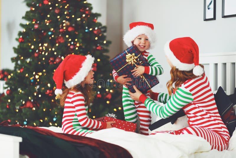Madre e bambini felici della famiglia in pigiami che aprono i regali su chr immagine stock libera da diritti