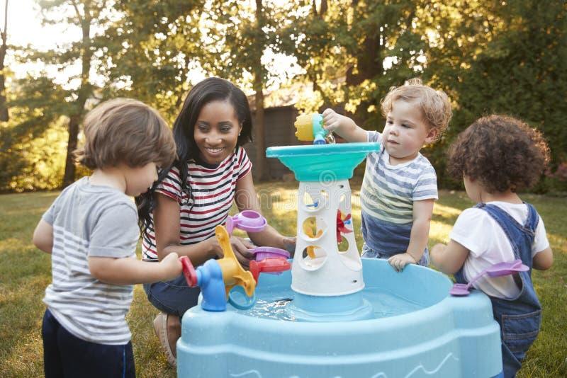 Madre e bambini piccoli che giocano con la superficie freatica in giardino immagine stock libera da diritti