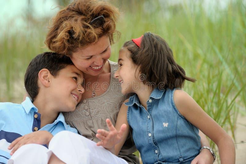 Madre e bambini sulla spiaggia immagine stock libera da diritti