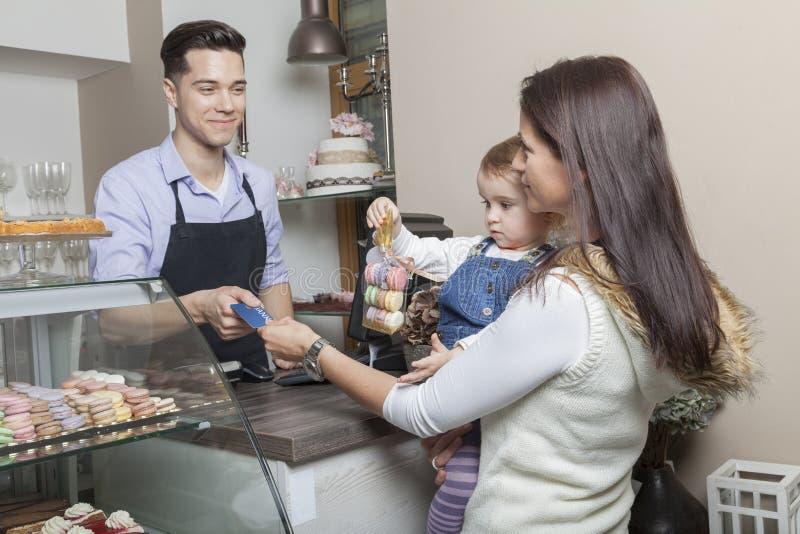 Madre e bambino alla cassa di una pasticceria immagine stock libera da diritti
