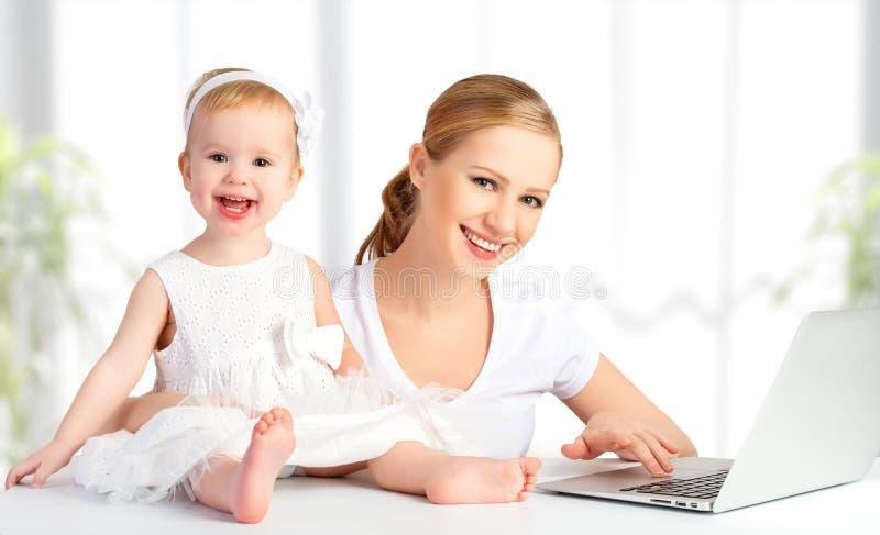 Madre e bambino a casa facendo uso del computer portatile fotografia stock libera da diritti