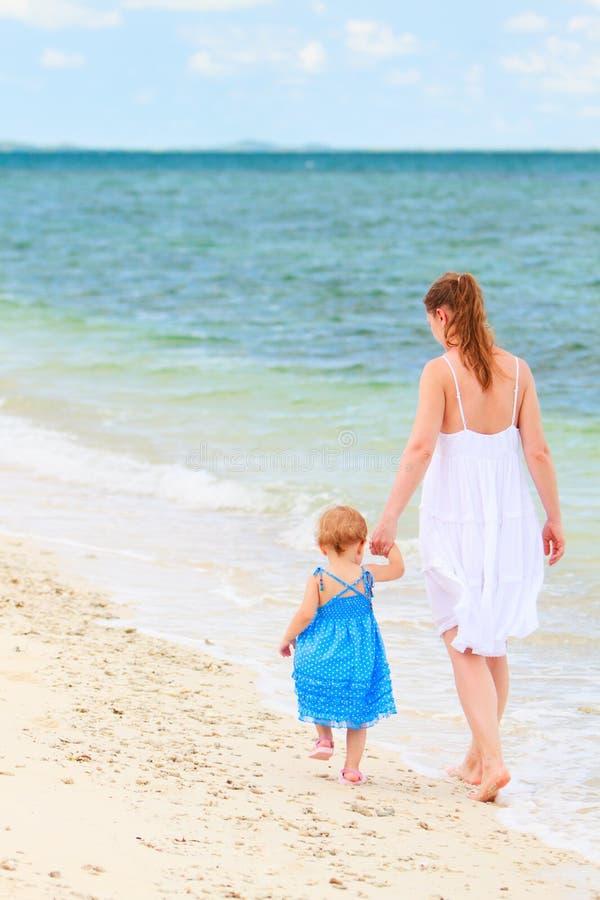 Madre e bambino che camminano lungo la spiaggia tropicale fotografie stock libere da diritti