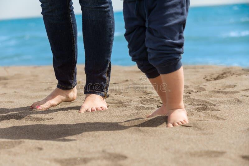 Madre e bambino che camminano su una spiaggia sabbiosa immagini stock libere da diritti
