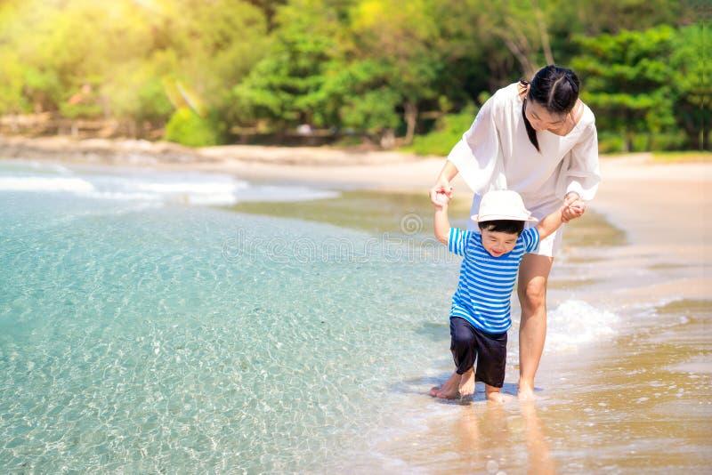 Madre e bambino che camminano sulla spiaggia fotografie stock libere da diritti